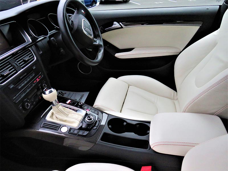 Interior vehicle detailing of white leather seats by Doctor Cuts